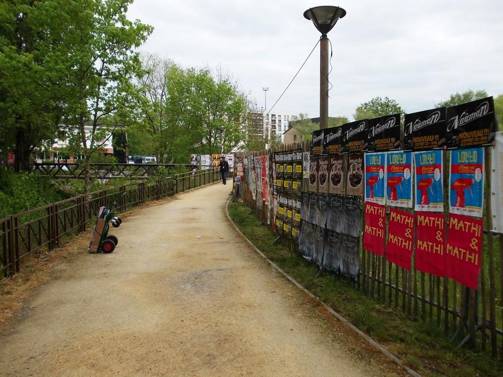 Pose d'affiches devant l'entrée des professionnels du W au festival du Printemps de Bourges