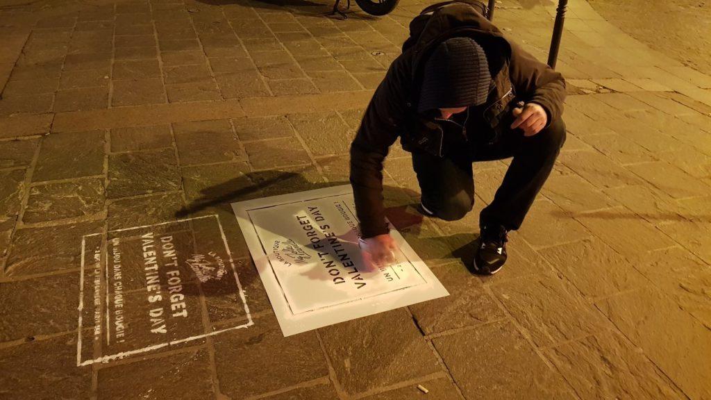 Un pochoir spray-tag de street art marketing pour la marque My Jolie Candle sur un trottoir à Paris