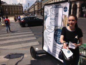 Distribution de flyers avec un vélo publicitaire d'affichage urbain mobile rue de rivoli à Paris au métro Louvre